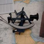 Sextant für die astronomische Navigation, nautische Tafeln und Seekarte