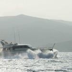 Große Motoryacht fährt durch eine Welle in schneller Fahrt.