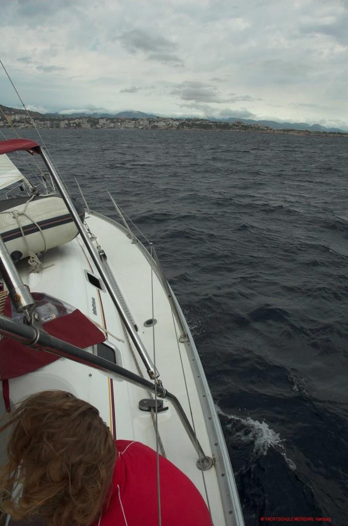 Segelyacht am Wind uns achteraus die Küste